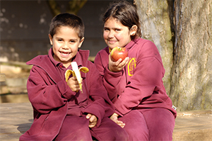 indigenous children smiling with fruit